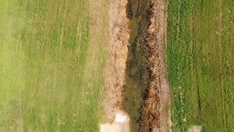 An aerial establishing shot flying along a flood control retention pond and drainage canal.