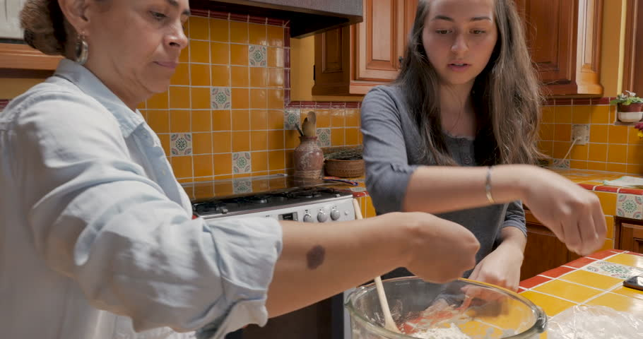 Latino mother and daughter sprinkling flour on dough while cooking and baking together in their kitchen | Shutterstock HD Video #1016338057