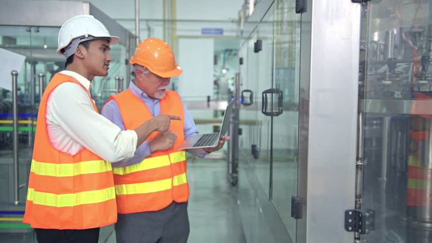 Senior quality inspector teaching junior team member in factory. Chinese old male with his young team discussing quality issue with bottle production line in background. | Shutterstock HD Video #1016349127
