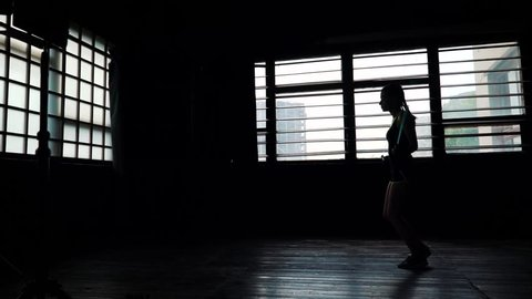 silhouette female boxer in wrapped bandage hands jumping on skipping rope in gym. Fit woman preparing to boxing competition. Wellness, fighting, motivation, martial arts, self defense concept