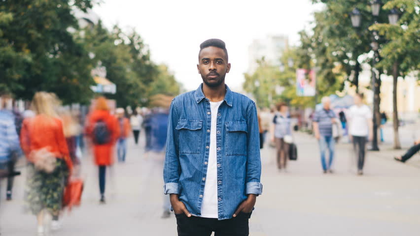 Zoom out time-lapse of stressed African American male looking at camera standing in the street in metropolis while crowds of people are whizzing around him. | Shutterstock HD Video #1016357107