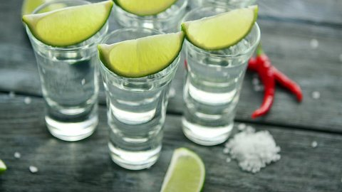 From above tequila shots served with lime and salt on wooden table with pepper