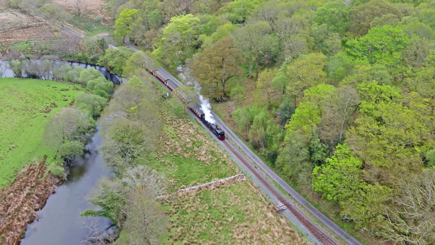 Aerial view of steam train driving through the Snowdonia National Park in Wales - United Kingdom.