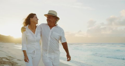 Happy romantic middle age couple enjoying relaxing sunset walk on the beach