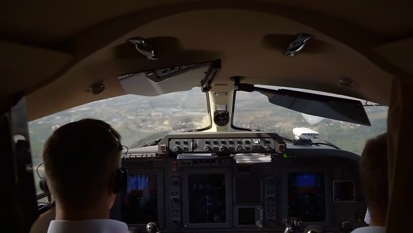 View from behind of two pilots in cockpit flying a plane, control panel with buttons and switches. | Shutterstock HD Video #1016380507