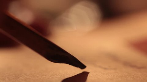 Close up reed pen writing fake arabic letters on papirus
