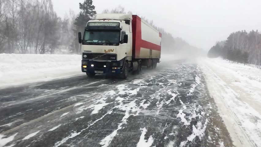 The car is on a snow-covered highway. Heavy truck with trailer carries cargo.  Winter road with a gusty wind and a snowstorm, slow motion.