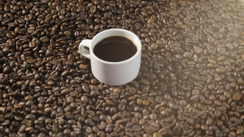 Coffee Cup and coffee beans. Women's hands draw a heart of coffee beans. A white Cup of steaming coffee with roasted beans around it.