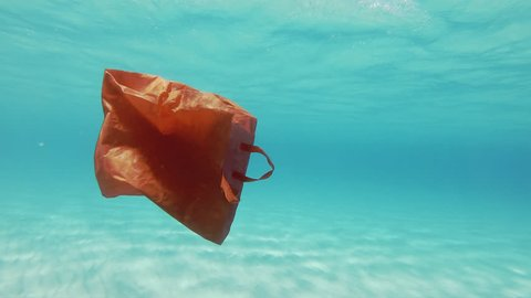 Plastic Pollution Underwater. Red Plastic Shopping Bag Floating Underwater In The Mediterranean Sea