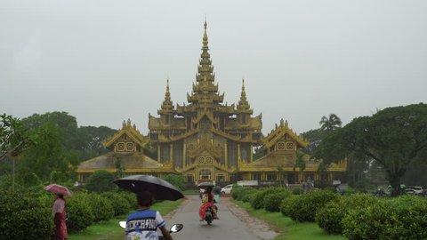 Bago, Myanmar - August 19,2018 : People in front of The Kambawzathardi Golden Palace (Palace of Bayinnaung) in Bago, Myanmar, in rainy day