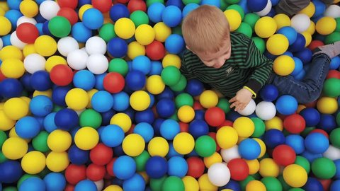 One happy smiling boy blond appears from multi-colored plastic balls and looks at the camera. Funny children's leisure with ball pits in the play pool, playground