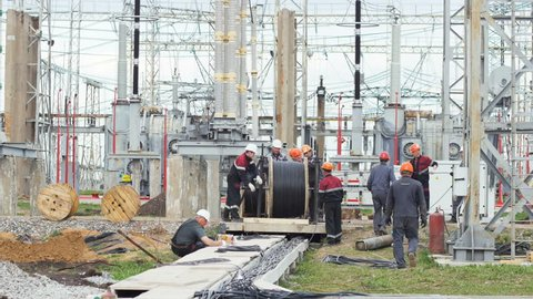 KAZAN, TATARSTAN/RUSSIA - MAY 28 2018: Strong working people turn large wooden bobbin and uncoil long wire at electrical distributing substation site on May 28 in Kazan