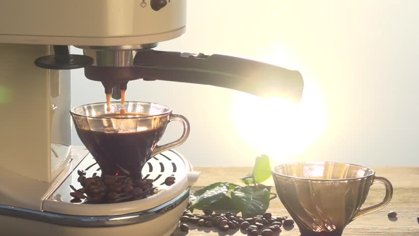 Coffee is poured from a coffee machine into a coffee cup illuminated by the sun's rays. Slow motion 240 fps. High speed camera shot. Full HD 1080p.