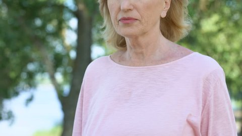 Adult woman having breathing problem, feels heart attack during walk in park