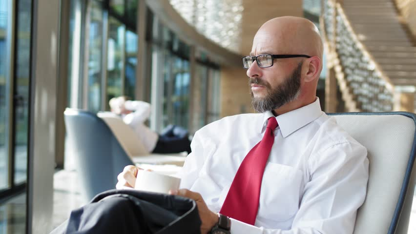 Thoughtful bearded businessman sits at the window after a hard day and drinks coffee in slow motion #1016457697