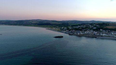 Drone flies slowly through the morning twilight to the Cornish town of Marazion. Shot from public land
