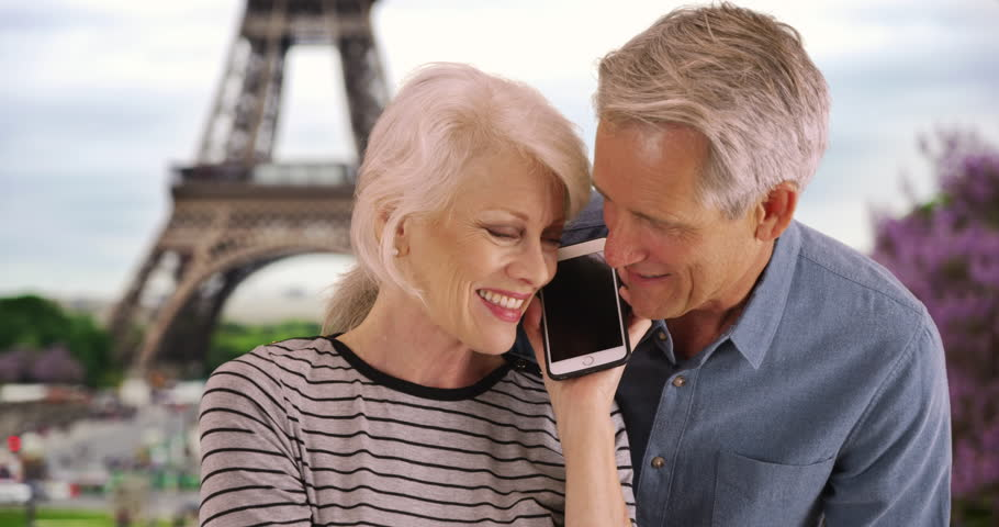 Portrait of senior couple talking on the phone in Paris. Smiling male and female chatting on smartphone near the Eiffel Tower. 4k | Shutterstock HD Video #1016466937
