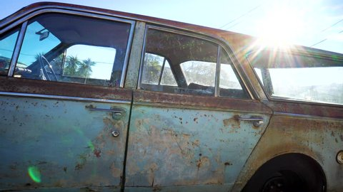 Old rusty Valiant car parked by busy intersection. Blue Valiant vintage looking grunge. Old abandoned classic car with lots of rust and flaked paint. 1960s surf wagon.