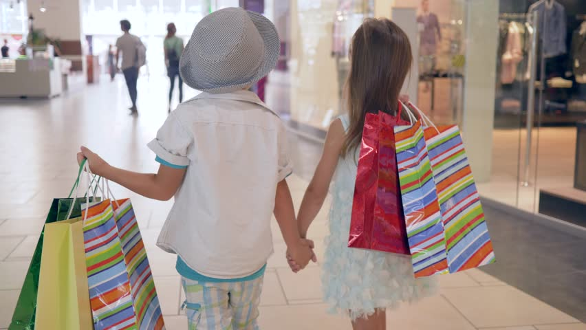 Children on shopping, stylish child friends with purchases into hands going by shop windows at mall after buy in expensive boutiques on weekends | Shutterstock HD Video #1016486647