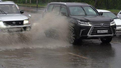 PETROPAVLOVSK CITY, KAMCHATKA PENINSULA, RUSSIA - 18 SEP, 2018: Japanese cars Toyota Land Cruiser Prado and Lexus drive on city street road over deep muddy puddle and splashing water from wheels.