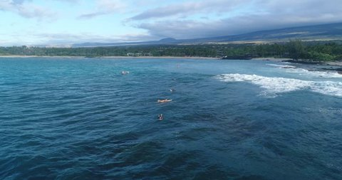 Slow motion aeril footage of a girl in bikini surfing a wave with a long beach and a conoe in the background in Kailua Kona, Hawaii