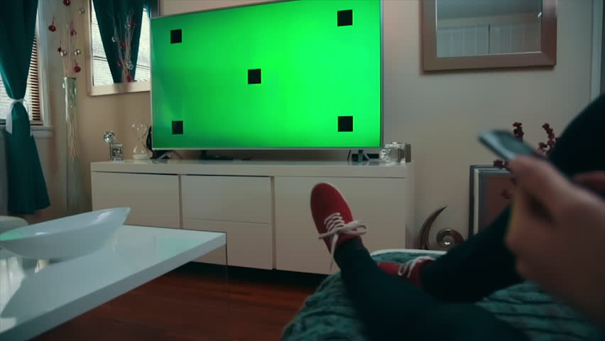 Medium Dolly Shot of a caucasian woman sitting comfortably in her living room, watching TV, and uses a remote to press a button. TV screen is set on green screen with tracking marks.