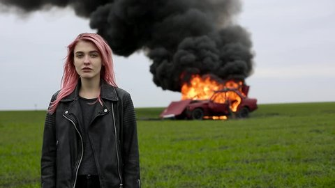 Young beautiful emo-girl with pink hair and in a leather jacket stands on the background of an exploding car, a hipster and a car explosion