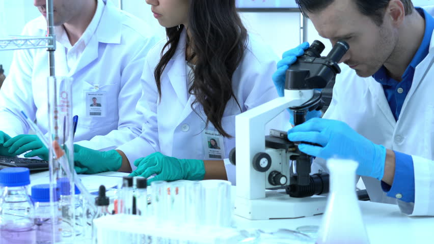 Scientist is looking through microscope with colleagues working in modern laboratory or medical center. Concept of science, testing development and lab industry. #1016538937