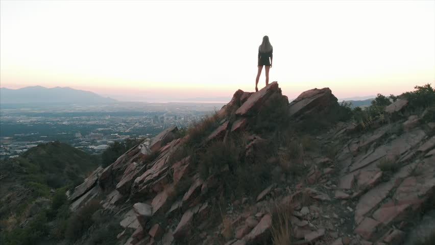 Aerial shot of woman hiker on top of mountain Salt Lake City Utah sunset