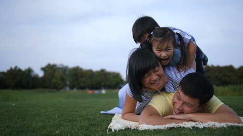 Multinational family with two cute little children lying and making a pile on grass in summer park during family weekend. Playful asian family of four making human pyramid while playing outdoors.