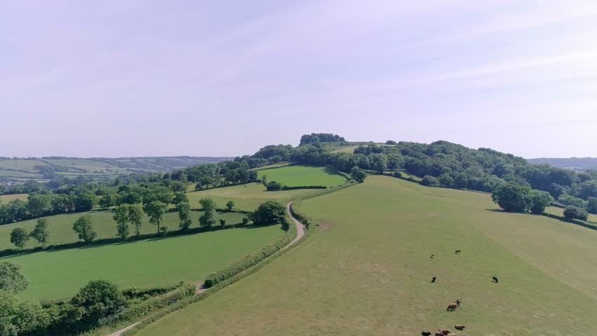 Forward tracking shot over fields and a country road towards a Neolithic fort of Dumpdon hill, East Devon, England
