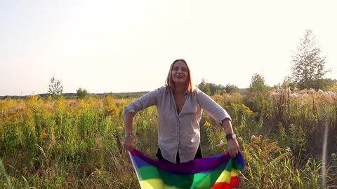 The woman with a rainbow flag in hands standing at the middle of the meadow at the forest.