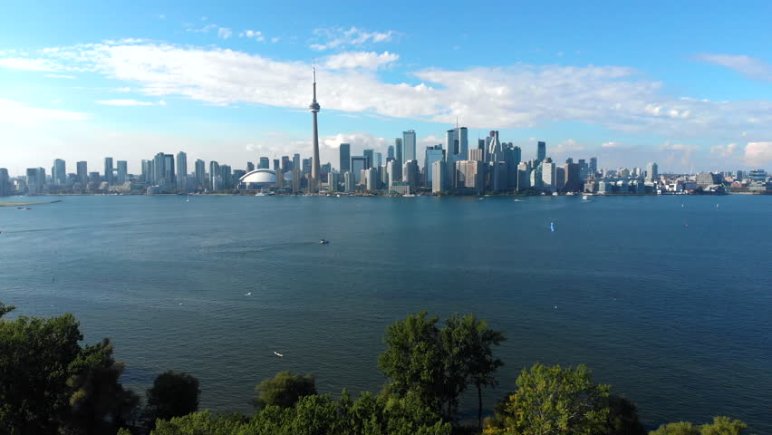 Aerial view of Toronto skyline, Centre Island and Lake Ontario during summer in Toronto, Ontario, Canada. Tilt up. | Shutterstock HD Video #1016565697