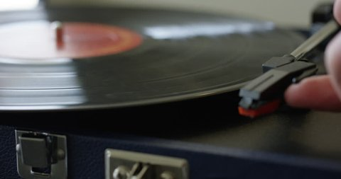 Man places retro record player needle onto vinyl - close up