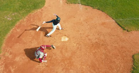 OVERHEAD CRANE Batter baseball player hits a ball over a home plate. 4K UHD 60 FPS SLO MO RAW