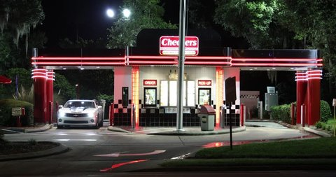 SEPTEMBER 19, 2018, INVERNESS, FL: Medium shot of dual drive-thru fast food restaurant, Checkers. It's bright neon exterior and hip retro look take customers back in time to the 1950s.