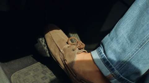 Close-up of male driver foot in shoes pressing brake pedal while driving car on road. Man foot pressing car brake pedal to avoid car accident during a drive.