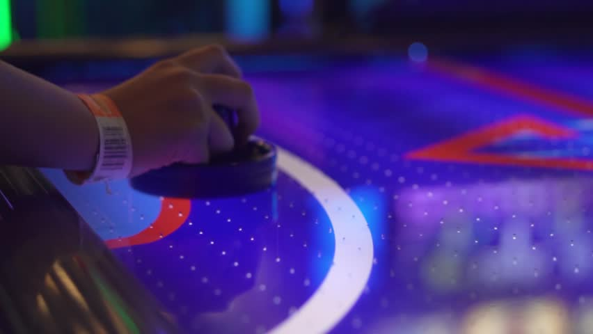 Slo-motion, side shot of a girl's hand playing air hockey.