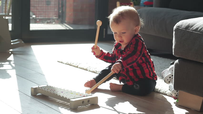 Baby boy playing xylophone at home