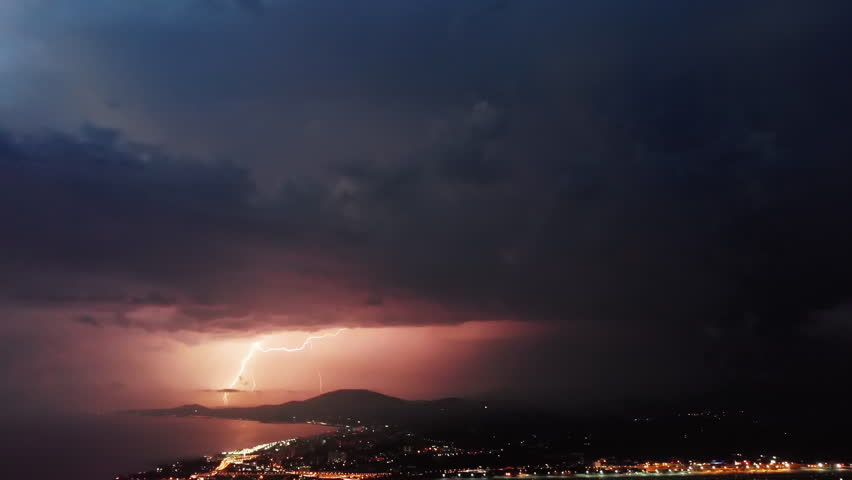 Timelapse of beautiful thunderstorm with picturesque lightning illuminating the sky with pink and orange colors. Many dramatic lightning flashes on the stormy sky over the night coastal city.