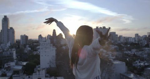 Beautiful woman on a rooftop opening her arms into the golden sunrise
