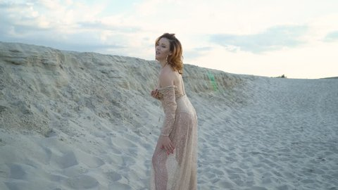 hot sandy desert at sunset. the woman gently tramples the sand and dances. It goes into the sunset. a long golden dress develops in the wind.