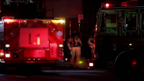 Firefighters getting ready to fight a building fire at night. Firetruck with flashing lights and fireman in uniform at night.