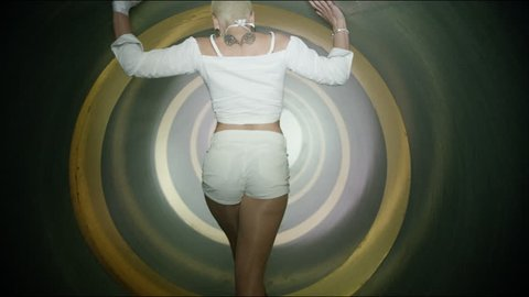 A beautiful blonde and sexy girl , woman dancing inside circle tube . Against yellow gold & gray background . Real decoration . None computer graphics . Shot on Arri Alexa Cinema Camera in 4K .