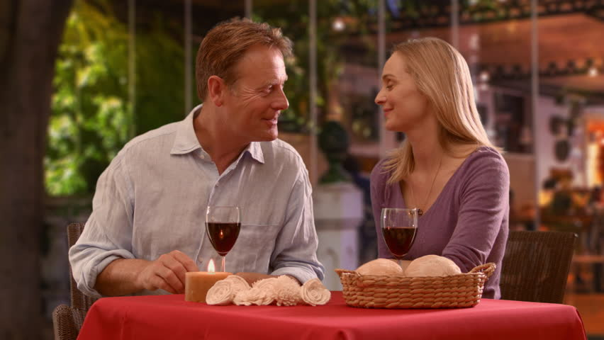 Mid aged couple in caf\x82 or restaurant with red wine and present