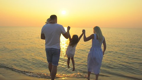 Happy family outdoors at beach sun sunset. Mother, father holding hands little girls child standing on sea sandy beach watching ocean at golden sunset Happy Family Travel Nature tourism happy holiday