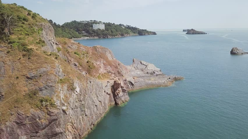 Drone ascending over the cliffs of Torquay in England. There are some smaller rock formations in the water, and islands near shore.