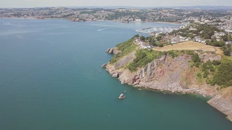 Aerial view of coastline in Torquay England. Panoramic view from the sky of beach town in southwest England. Blue ocean water, cliffs, and amazing landscape is visible.