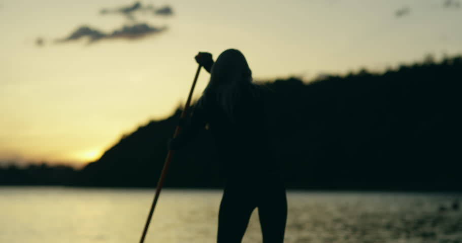 Young woman on a stand up paddle board exercising at sunset on a lake in Sweden. Slow motion and silhouette looking imagery.