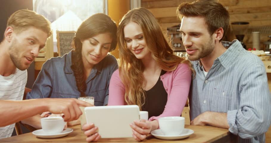 Group of Caucasian friends using digital tablet in cafe 4k | Shutterstock HD Video #1016828017